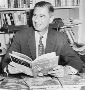 Ted Geisel (Dr. Seuss) half-length portrait, seated at desk covered with his books / World Telegram & Sun photo by Al Ravenna